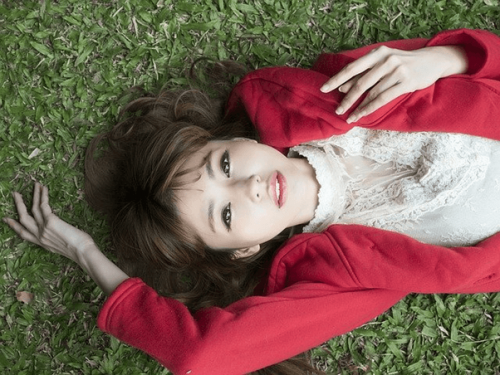 草原に寝転ぶ若い女性